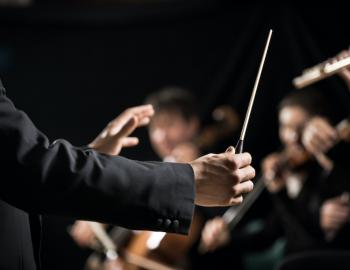 A conductor leads an orchestra