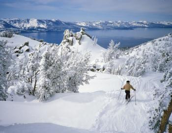 A person skis down a snowy mountain's groomed slope overlooking Lake Tahoe