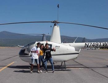 people standing next to a helicopter