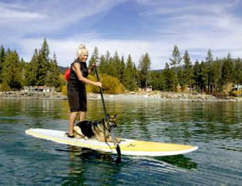 woman and dog on a stand up paddle board