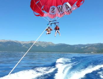 two people parasailing behind boat