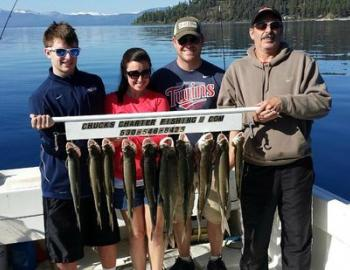 four people holding a stick with the fish they caught