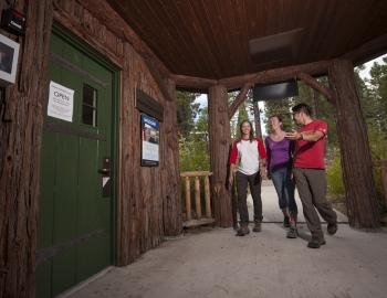 three people walking into the front door of a cabin