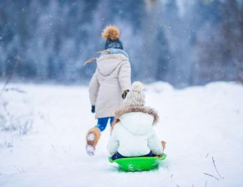 child pulling a child on a snow sled