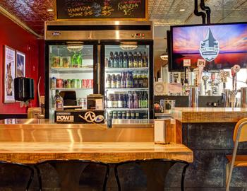 front counter for ordering with refrigerator with drinks in the background