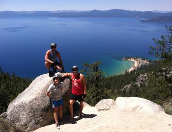 three people on boulders high above the tahoe waters