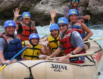 people in large white water raft in river