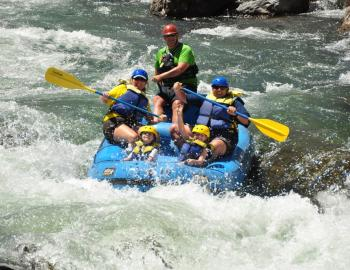 people in a large white water raft going down the river