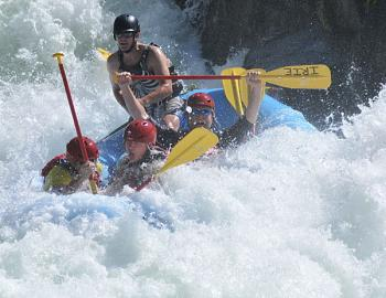 people in rough white water in a large raft