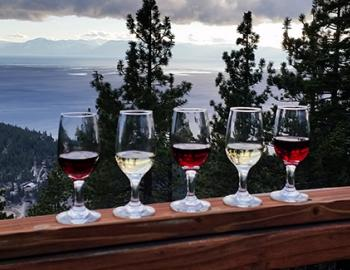 wine glasses on railing with view of lake