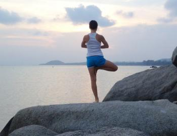 woman on rock in a yoga pose