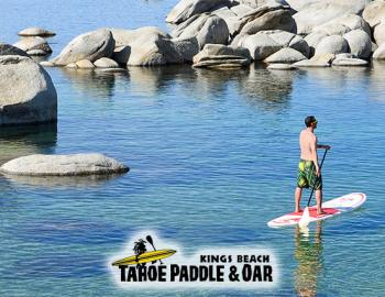 man on stand up paddle board on calm waters with boulders in water around
