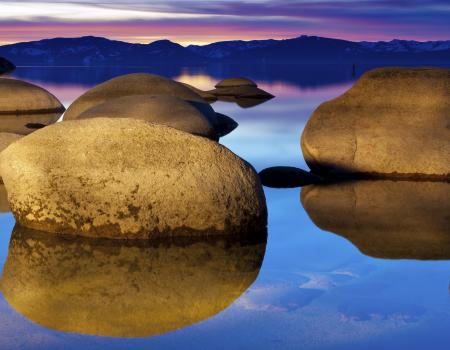 large boulders on the lake at sunset