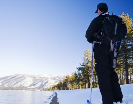man standing still on skis looking at the snow