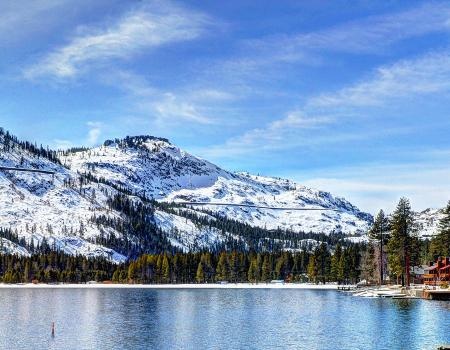 donner lake with snow capped mountains on the other side of the lake