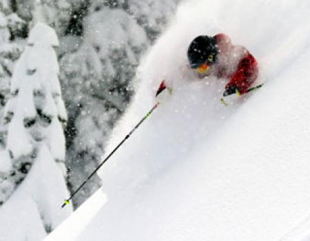 man skiing through fresh powder