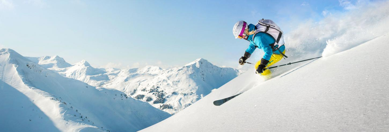 man skiing down hill in fresh powder