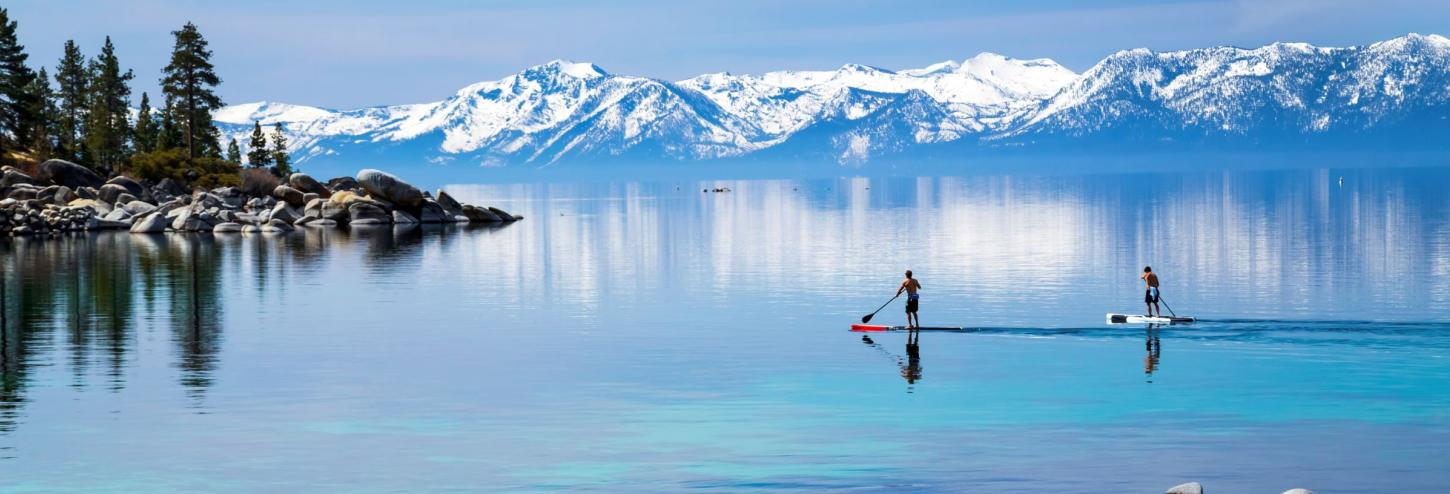 stand up paddle boarders on calm lake tahoe waters with snowy mountains in the background