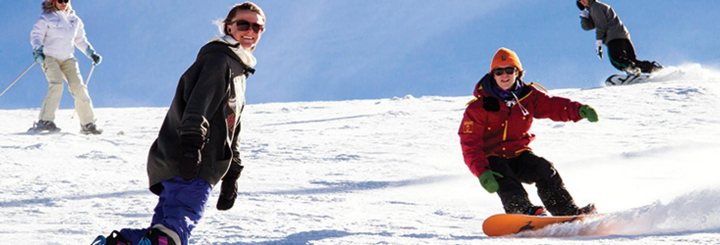 two people snowboarding down a mountain
