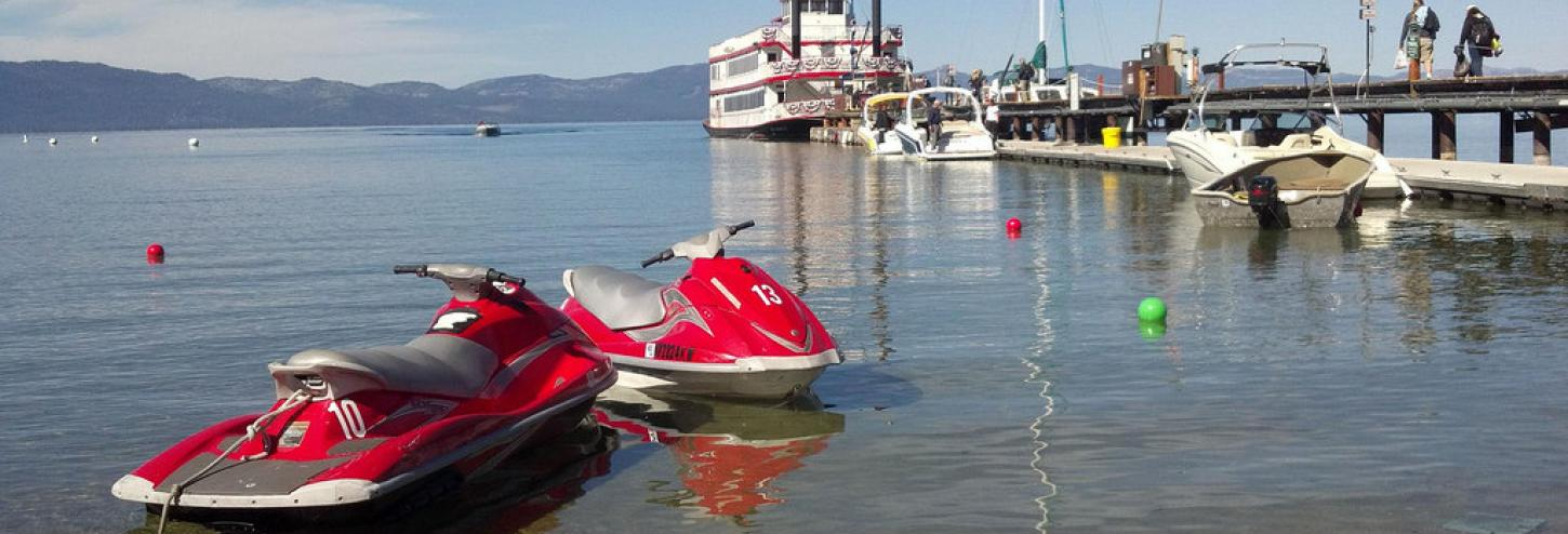 jet skis and docked boat in background