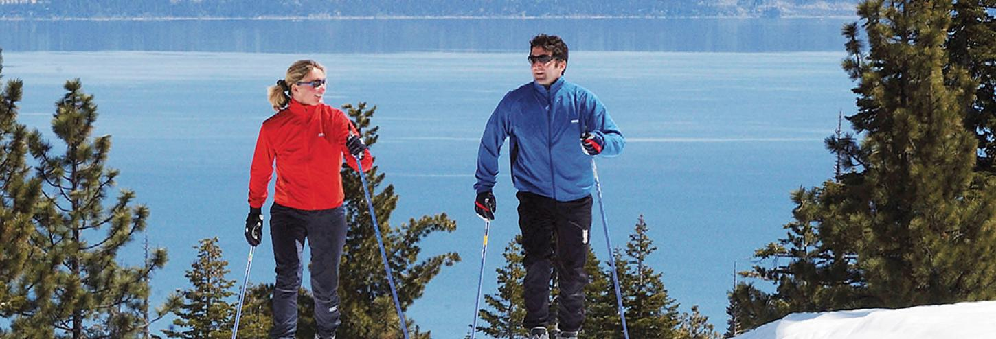 two people cross country skiing with lake in the background
