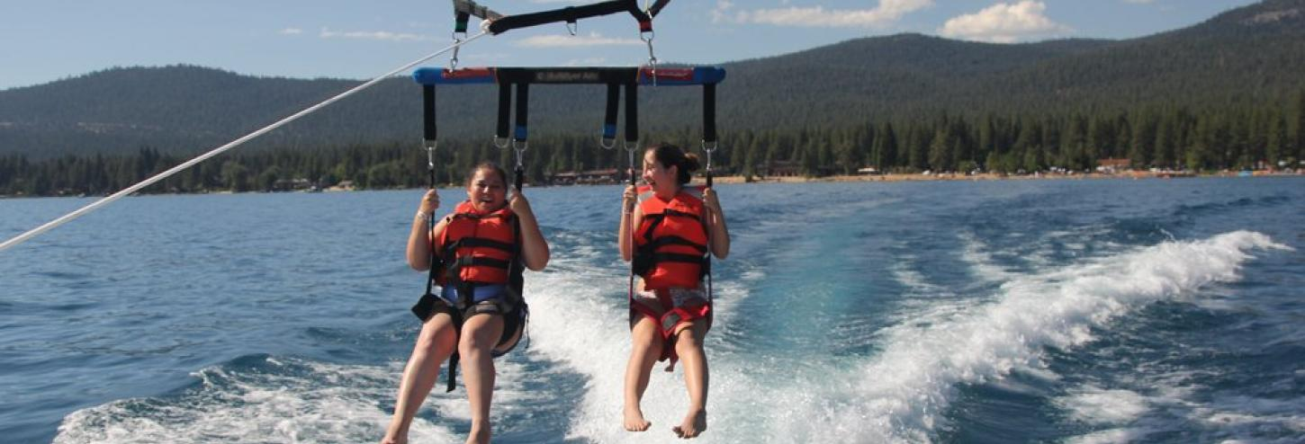 two girls parasailing behind boat feet almost touching the water