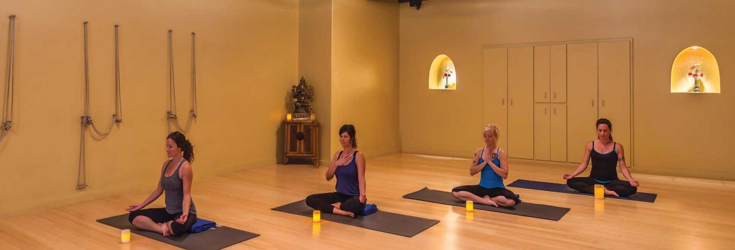 women in a yoga room in a yoga pose