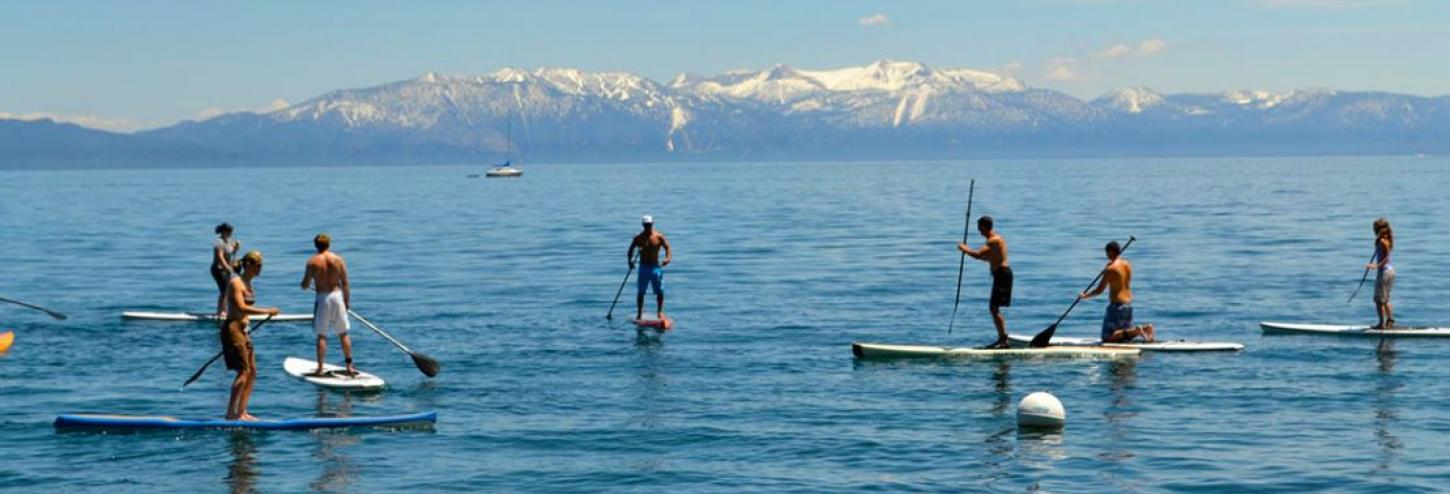 many people on stand up paddle boards in tahoe