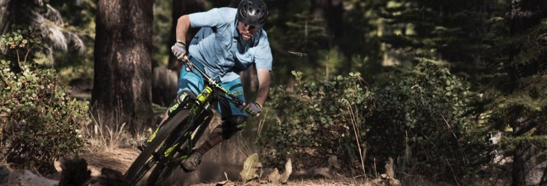 man riding a mountain bike downhill wearing a helmet