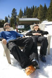 skiers relaxing on chairs in sunshine