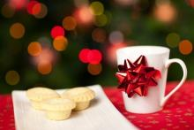 white cup with red ribbon next to a plate of snacks for sants